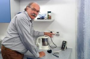 Energie-Sparhelfer Günter Kramer misst in einem Haushalt den Stromverbrauch eines Wasserkochers.
